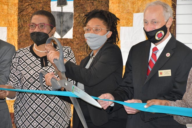 Shineece Sellars is flanked by Dr. Pamela Moye and Alamance Commissioner John Paisley as she cuts the ribbon on the African American Cultural Arts and History Center in downtown Burlington.