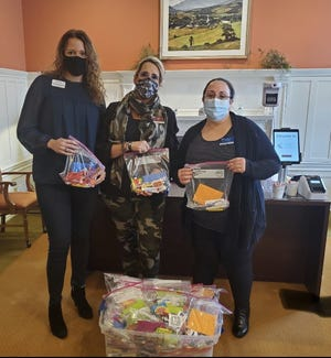 From left: Jenna Petrenko, Teresa Burns and Lindsay Nelson. Burns received travel items donated by Compass on the Bay, a Memory Support Community in South Boston.