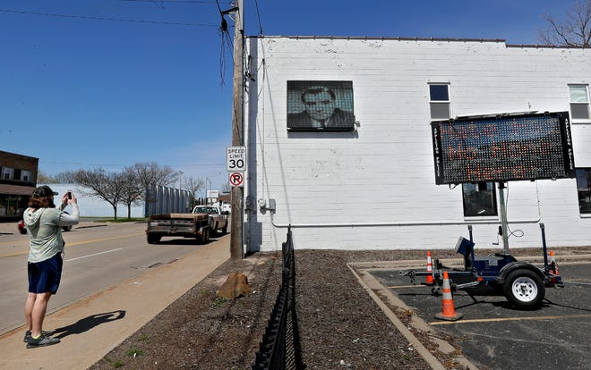 """Alexander Cullen, who moved to Appleton in February, stops to take a picture of competing signs on Friday in Appleton. In response to a sign with homophobic language on a building along Richmond Street, the city of Appleton has placed a sign nearby that reads """"Hate has no home here."""""""