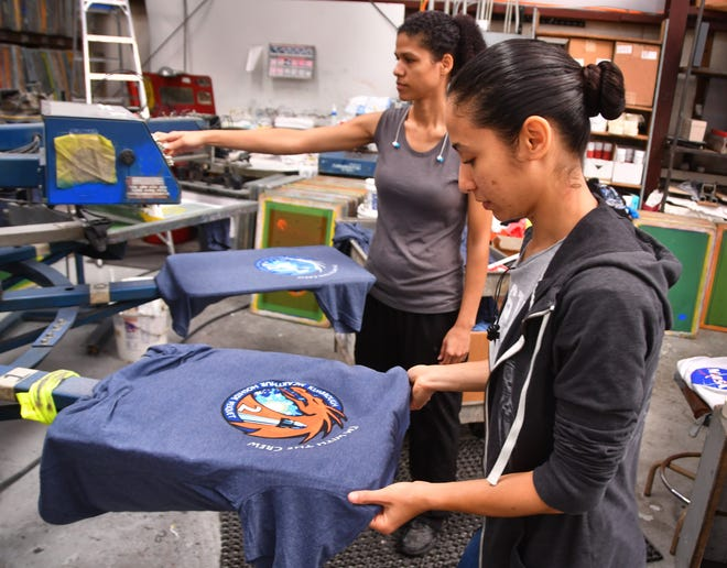 """Rosa Ross and Nancy Ross print souvenir launch T-shirts at Space Shirts on Merritt island. The shirts depict the Crew Dragon Crew-2 mission patch, with the phrase """"I'm with the crew"""" added above the patch.  - dd349b5d 98e7 4d72 a311 0e2d687cfadf Launch tourism 1 - Space Coast tourism expects boost from SpaceX launch of astronauts"""
