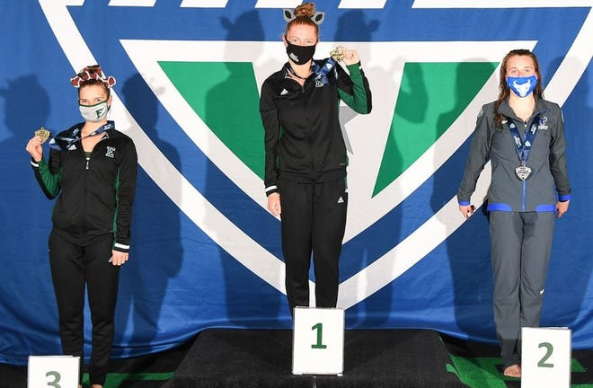 Eastern Michigan senior Bethany Berger, middle, with her MAC championship medallion.