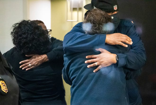 Orang-orang berpelukan setelah mengetahui bahwa orang yang mereka cintai aman setelah penembakan di dalam gedung FedEx pada hari Jumat.