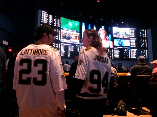 FILE - In this Sept. 9, 2018, file photo, football fans wait for kickoff in the sports betting lounge at the Ocean Casino Resort in Atlantic City, N.J.