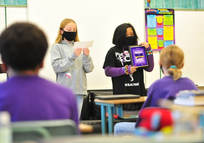 Loy Elementary School students Leah Fowler and Reynalynn Tongohan show off a plaque indicating that Loy is part of the Purple Star Schools program, which is a program that supports students of active military families.