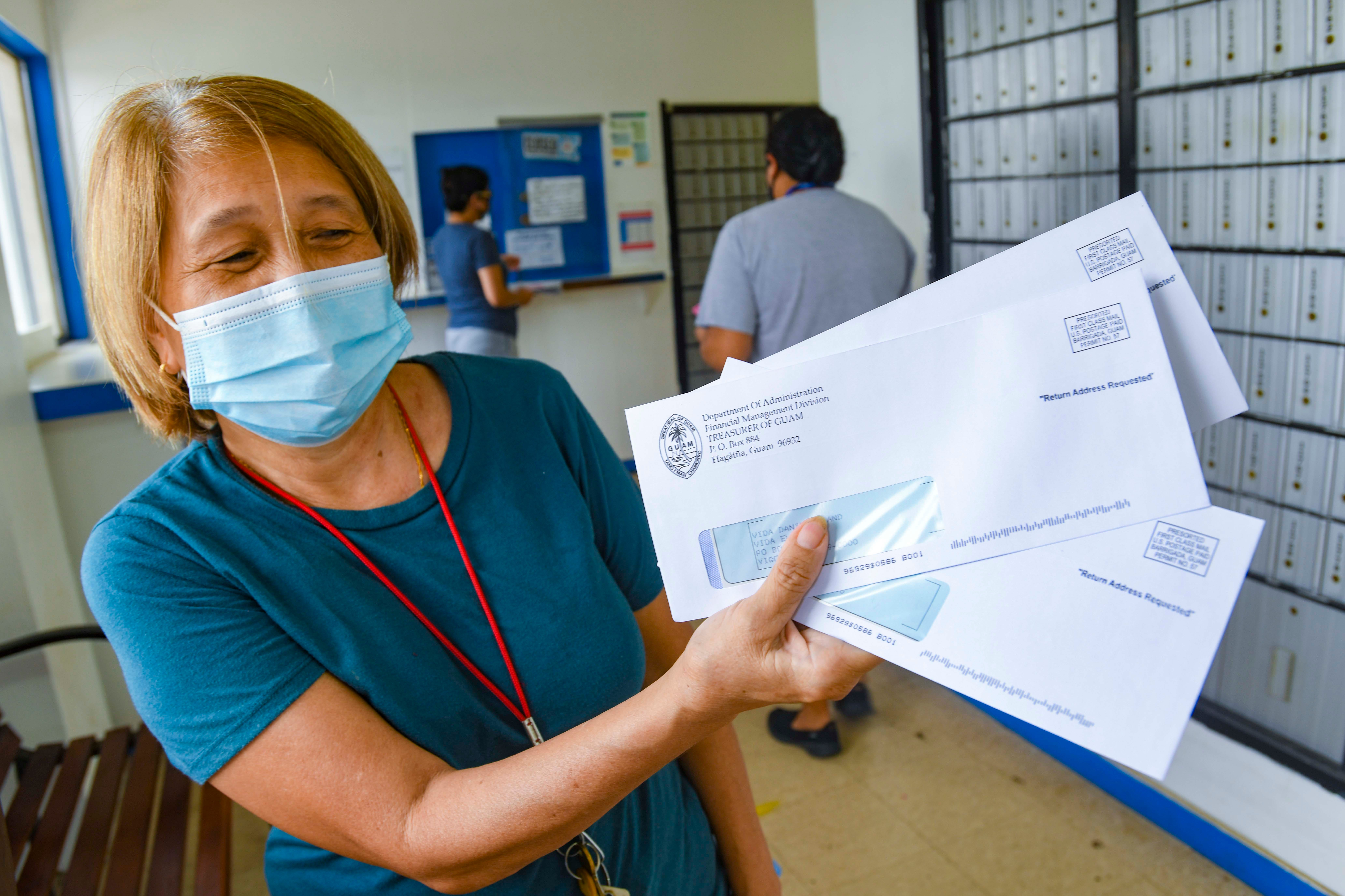 Yigo resident Elisa Vida shows three envelopes containing stimulus checks for her and other household members she received after checking her mailbox at the post office in Yigo in this April 16 file photo. The Department of Administration has publisheda list of individuals with uncashed Economic Impact Payment checks, also known as stimulus checks, on its website.