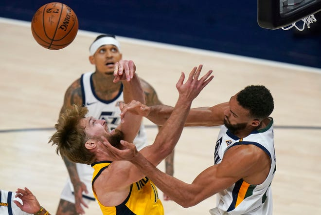 Indiana Pacers forward Domantas Sabonis, left, and Utah Jazz center Rudy Gobert, right, vie for a rebound during the second half of an NBA basketball game Friday, April 16, 2021, in Salt Lake City. (AP Photo/Rick Bowmer)