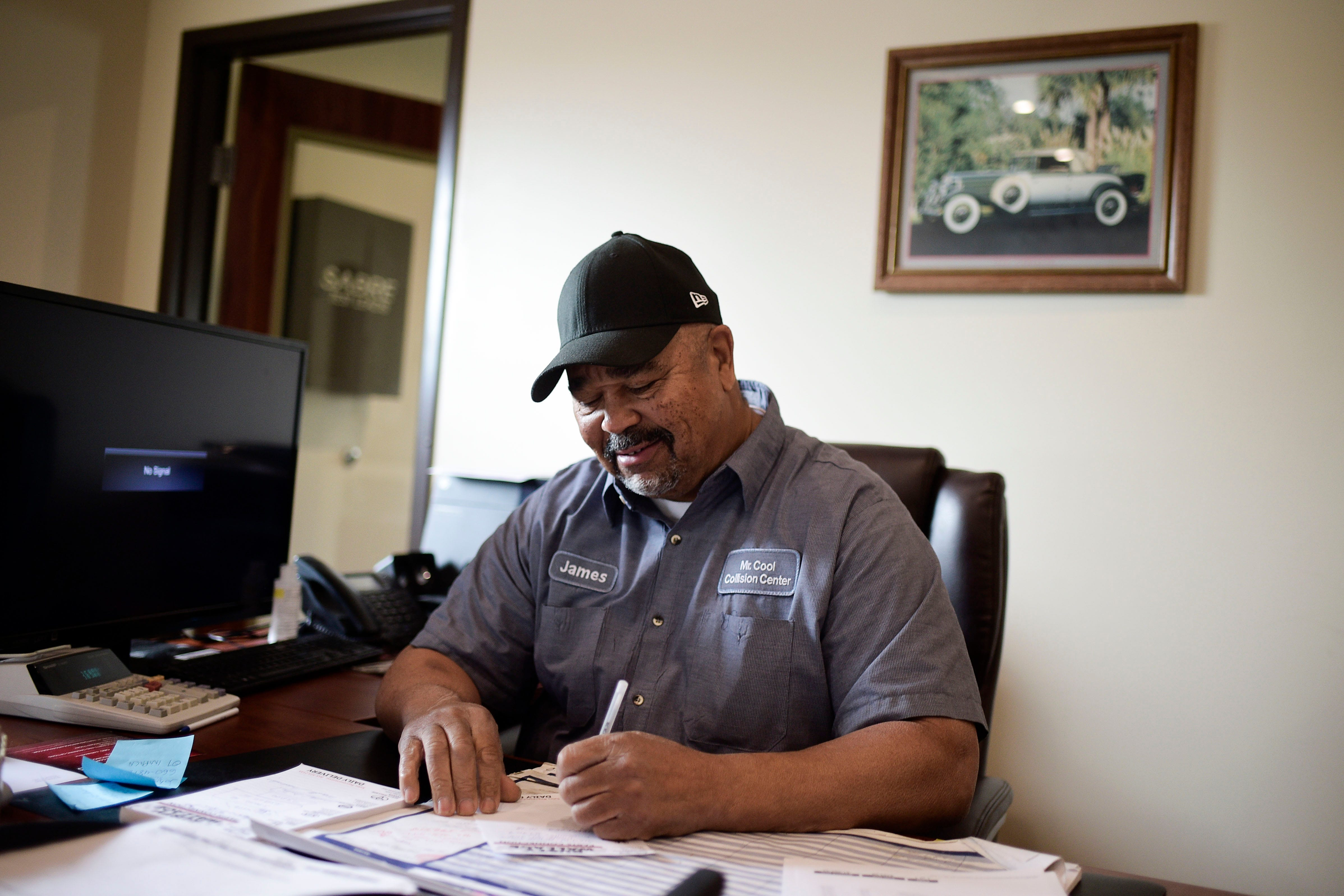 James Brown, aka Mr. Cool, works at his desk at Mr. Cool Collision on Gleason Dr. in Knoxville, Tenn. on Friday, April 16, 2021.