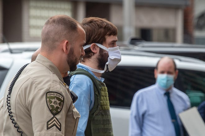 Ian Howard, 31, accused of first-degree murder in the Oct. 1, 2017, shooting death of Lafayette Cpl. Michael Middlebrook, is escorted to the Lafayette Parish Courthouse on Friday, April 16, 2021.