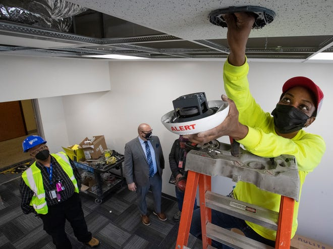 Journeyperson electrician Stephanie Key installs a smoke alarm at Milwaukee Area Technical College's downtown campus Friday, April 16, 2021, in Milwaukee. She works for Hurt Electric Inc.