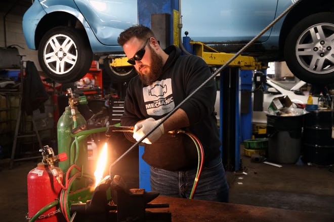 Elijah Corona, owner of The Family Mechanic, welds a metal rod on Thursday in his shop in Bay View. The rod will be used to protect a catalytic converter on a car from theft. There has been an uptick in theft of catalytic converters, with nearly 500 stolen from cars this year in Milwaukee. The Hyundai behind him recently had the rods installed.