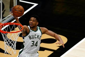 Bucks forward Giannis Antetokounmpo scores on a finger-roll against the Hawks.