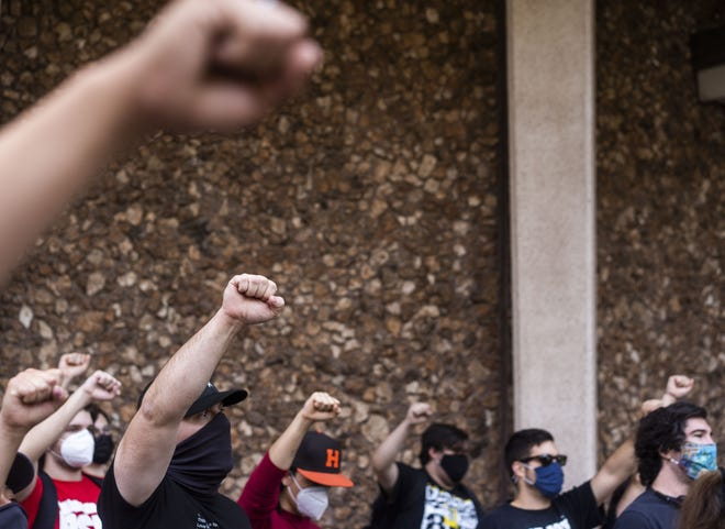 Attendees hold their fists in the air during a rally against police brutality at Cesar Chavez Plaza at Phoenix City Hall on Washington Street in downtown Phoenix on April 15, 2021.