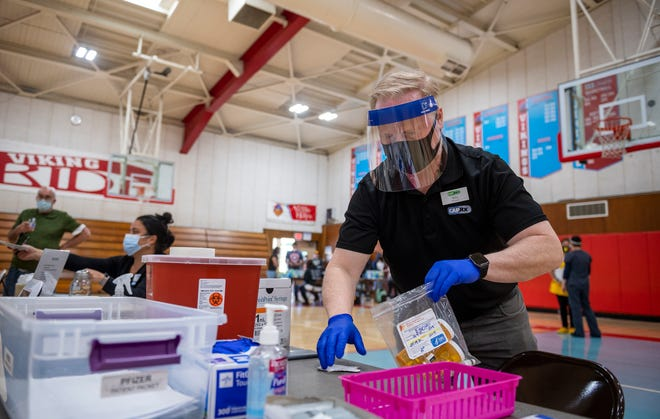 Whit Snow, a pharmacist at Central Avenue Pharmacy, holds a bag full of Pfizer COVID-19 vaccine containers at North Salinas High School in Salinas Calif., on Thursday, April 15, 2021.