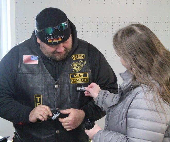 Lynn Gauer, volunteer coordinator in Ipswich for Feeding South Dakota, presents volunteer Scott Hagen with a Feeding South Dakota patch.