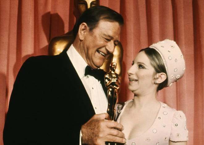 John Wayne accepts his Best Actor Oscar from US singer and actress Barbra Streisand in 1969.