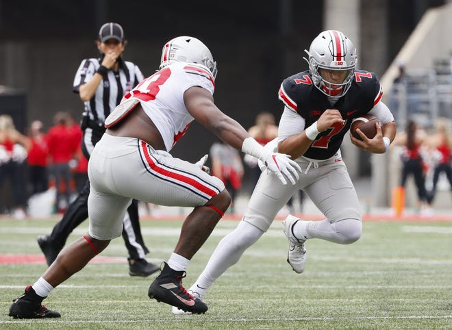 Quarterback C.J. Stroud, here running past defensive end Cormontae Hamilton, completed 16 of 22 passes for 185 yards and two touchdowns in Saturday's spring game.
