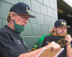Lake Minneola coach Kerry Whetro looks over his scorebook while talking with pitcher Parker Fenton (39) during Thursday's game against Real Life Christian Academy in Minneola. Fenton was the winning pitcher in a 4-2 win in what was Whetro's 500th career victory. [PAUL RYAN / CORRESPONDENT]