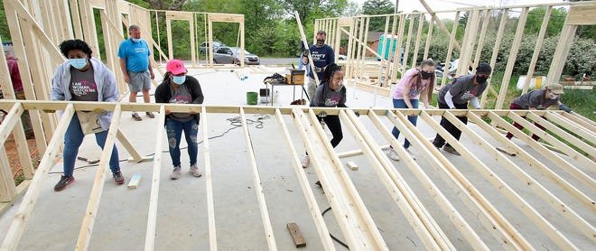 A group of women lift a wall into place as women with Habitat for Humanity work during the initial build for a new house on Gidney Street in Shelby Saturday, April 17, 2021.