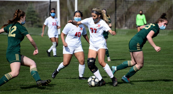 Alex Yoder of Huron controls the ball from Emma Zaleski (left) and Caroline Roecker of SMCC as Huron won the match 3-1 Friday, April 16, 2021. Behind for Huron Marianna Gonzalez.