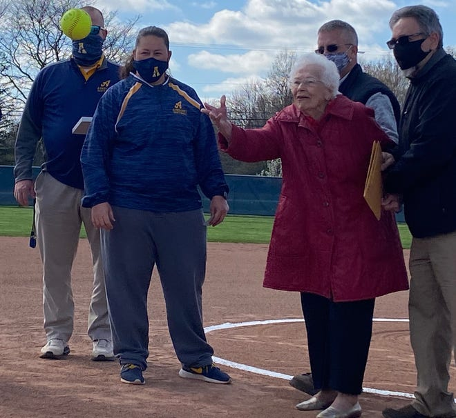 Anna Renaud, 94, throws the first pitch Friday prior to a game against New Boston Huron to dedicate the newly renovated softball diamond at Airport High School. Renaud was honored for donating money to fund a new press box, locker room, concession area and restroom. To Renaud's right are Airport superintendent John Krimmel and softball coach Jess Irwin.