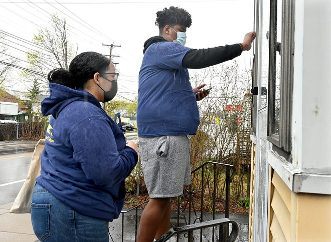 Alondra Ledesma, left, 15, and JoJo Dos Reis, 17, both of Framingham, knock on a door to educate residents in about the importance of getting the COVID-19 vaccine, April 17, 2021.