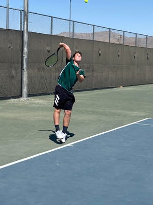 Tucker Anderson serves against one of Apple Valley's singles players on Friday night.
