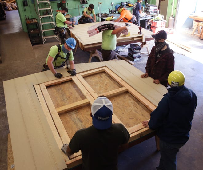 Volunteers, carpentry students and teachers assemble walls of sheds at the McKenzie High School wood shop in Blue River on Saturday. The sheds will be assembled on sites around the valley later for people who lost their homes and businesses to the Holiday Farm Fire.