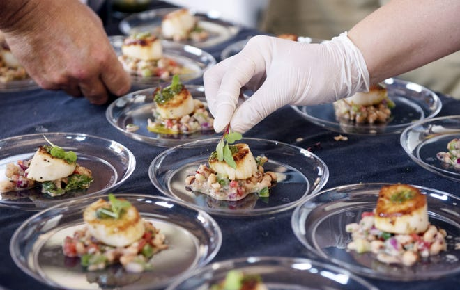 In this St. Augustine Record file photo, Justina Gulledge from the Aviles Restaurant at the Bayfront Hilton places the garnish on a fresh pan-seared scallop with black-eyed peas, as a customer grabs a finished sample plate from the other side of the table during the Taste of St. Augustine food festival at the St. Augustine Amphitheater on Saturday, April 22, 2017.