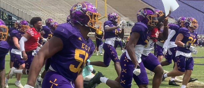 East Carolina's defense celebrates after a pick-six near the end of its first spring scrimmage on Saturday at Dowdy-Ficklen Stadium.