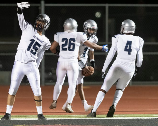 Silverado's Eric West, left, celebrates after Darren Gandy, second from right scored a touchdown against Adelanto during the fourth quarter Friday, April 16, 2021.