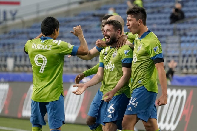 Seattle Sounders midfielder Joao Paulo (6) celebrates with forward Raul Ruidiaz (9) and midfielder Josh Atencio, right, after Paulo scored a goal against Minnesota United during the second half of an MLS soccer match, Friday, April 16, 2021, in Seattle.
