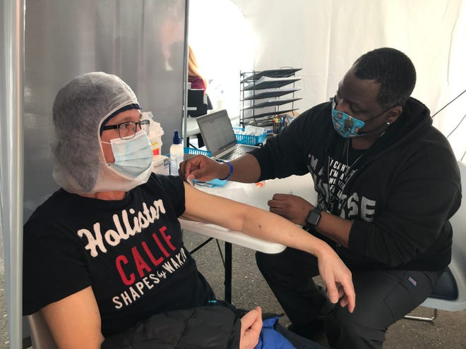 Christopher Jones, right, a nurse with Project HOPE, administers the Moderna COVID-19 vaccine to Danh Tran at the healthcare nonprofit's downtown office.