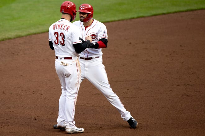 Cincinnati Reds right fielder Nick Castellanos (2) celebrates with Cincinnati Reds right fielder Jesse Winker (33) after they both reached base in the ninth inning of the MLB baseball game between Cincinnati Reds and Cleveland Indians at Great American Ball Park in Cincinnati on Saturday, April 17, 2021.