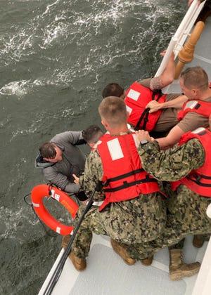 Dalam foto ini disediakan oleh Penjaga Pantai AS, anggota kru Penjaga Pantai Cutter Glenn Harris menarik seseorang dari air pada Selasa, 13 April 2021 setelah perahu angkat komersial setinggi 175 kaki terbalik 8 mil di selatan Grand Isle, La.