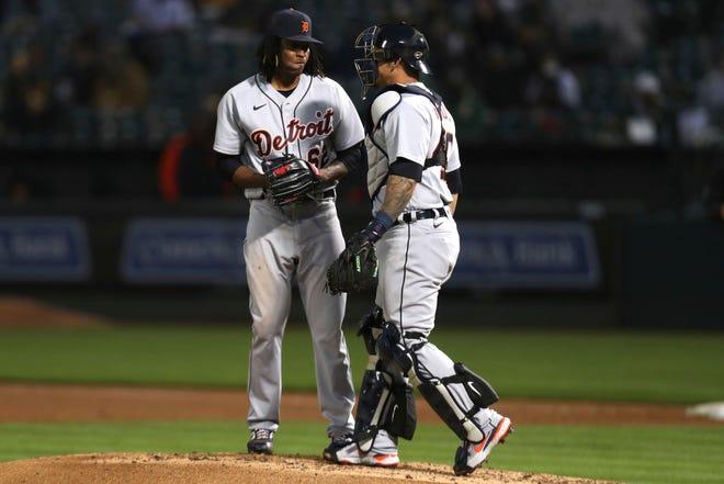 Pelempar Detroit Tigers Jose Urena, kiri, berbicara dengan penangkapnya Wilson Ramos setelah menyerah dua kali berlari ke Oakland Athletics selama inning keempat.