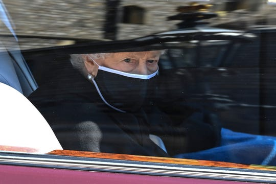 Britain's Queen Elizabeth II follows the coffin in a car as it makes it's way past the Round Tower during the funeral of Britain's Prince Philip inside Windsor Castle in Windsor, England, Saturday April 17, 2021.