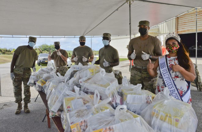 U.S. Air Force Airmen assigned to the 36th Civil Engineering Squadron and Kylani Ogo, Miss Voluptuous Pacific and Yona resident, participate in a COVID-19 relief food distribution event at the community gym in Yona, Guam, April 15, 2021. The 36th CES is Yona's sister squadron, as part of the Andersen Air Force Base Sister Village Sister Squadron program, through which squadron members collaborate with Guam residents in activities to strengthen their friendship and partnership. (U.S. Air Force photo by Alana Chargualaf)