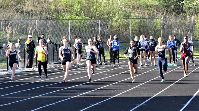 Girls' sprinters from Granville and Lancaster compete in the 100 during Friday's Granville Invitational.