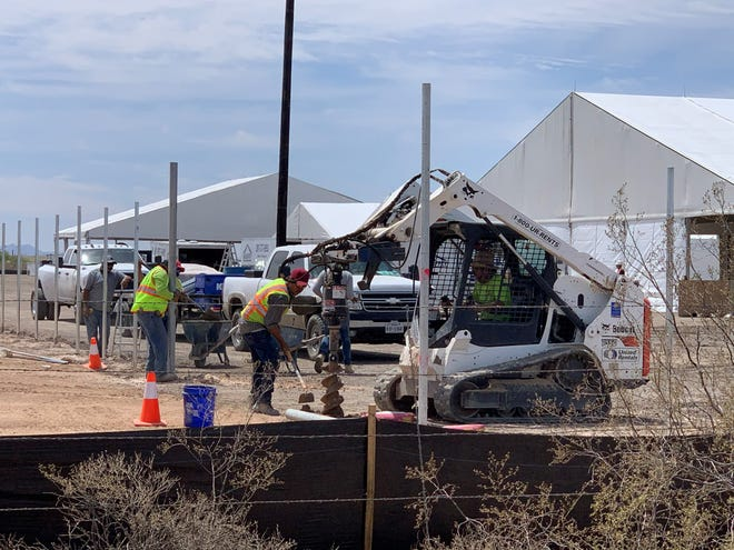 """Construction workers install on April 14, 2021, metal poles that will fence in a """"soft-sided facility,"""" a collection of tents going up in Tucson that will house migrants apprehended at the Arizona border, including migrant children."""