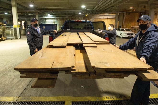 Architects of the Capitol staff hold rare century-old mahogany obtained from a U.S. Forest Service lab storage locker in Wisconsin. This historic mahogany lumber, received from USDA Forest Service's Forest Products Laboratory, will be used to replace U.S. Capitol doors and other wood details damaged during the January 2021 breach. (Architect of the Capitol/TNS)