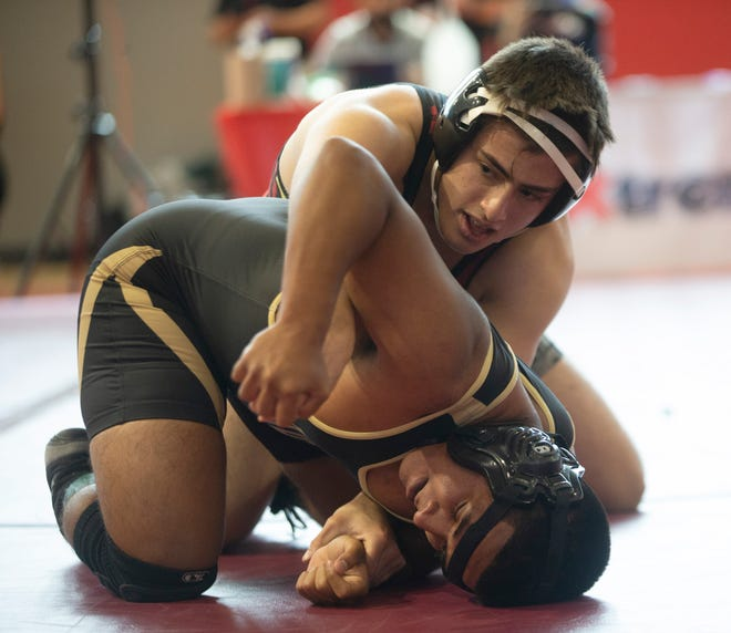 Brandon Orozco, at front, of Austin High School and Miguel Macias of El Dorado High School wrestle in the 160 lbs. division during the 1-5A wrestling tournament at Bel Air High School in El Paso, Texas on April 16, 2021.