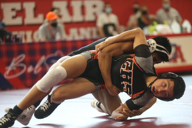 Lubbock High's Zach Casias, in white headgear, competed during an April 16 match in the 120-pound division against Caprock's Richard Davila at the Region I-5A wrestling tournament at Bel Air High School in El Paso.