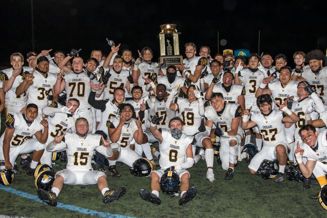 The Ventura High football team poses with the trophy after beating rival Buena 28-25 on Friday, April 16, 2021.