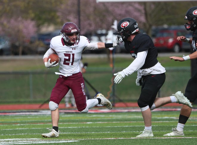 Harrison's A.J. Troilo delivers a stiff arm during the team's game against Rye at Rye High School on April 17, 2021.