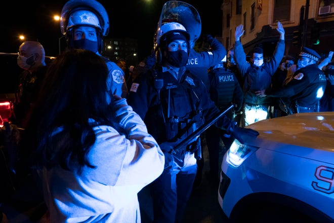 Protesters confront Chicago Police following a march for 13-year-old Adam Toledo Friday April 15, 2021 in Chicago's Logan Square neighborhood.
