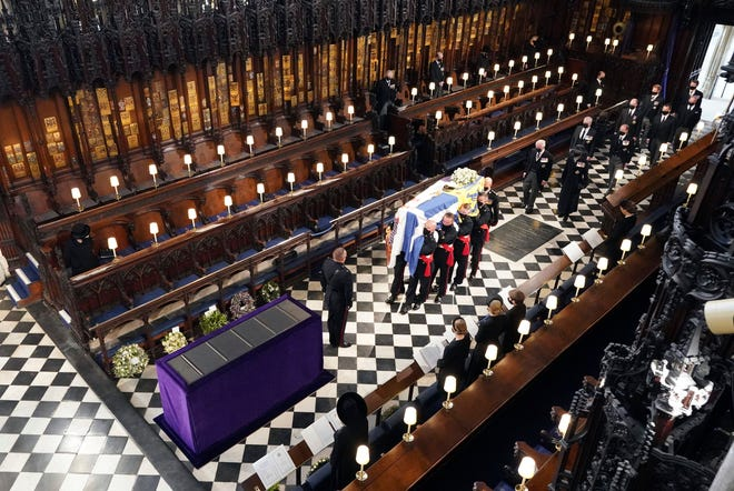Britain's Queen Elizabeth watches as pallbearers carry the coffin of the Duke of Edinburgh during his funeral at St George's Chapel in Windsor Castle.