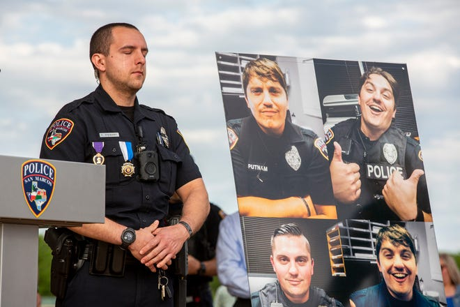 San Marcos police officer Franco Stewart becomes emotional while standing near a poster of slain officer Justin Putnam during a memorial at Five Mile Dam Park's soccer complex in San Marcos on Sunday, April 18, 2021. Stewart was with Putnam and officer Justin Mueller when they were ambushed and shot at during a disturbance call on April 18, 2020. Putnam died at the scene while Franco and Mueller sustained life threatening injuries. Franco received the Purple Heart along with the Medal of Honor for his actions during the incident.
