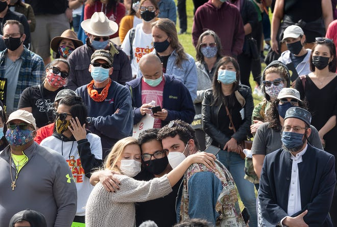 """From left, Alicia Roth Weigel, human rights commissioner for the City of Austin, Muneeb """"Meebs"""" Aslam and AJ Majd, co-founder of Embrace Austin, share a group hug as they listen to speakers during the Stop Asian Hate rally and vigil Saturday at Huston-Tillotson University."""