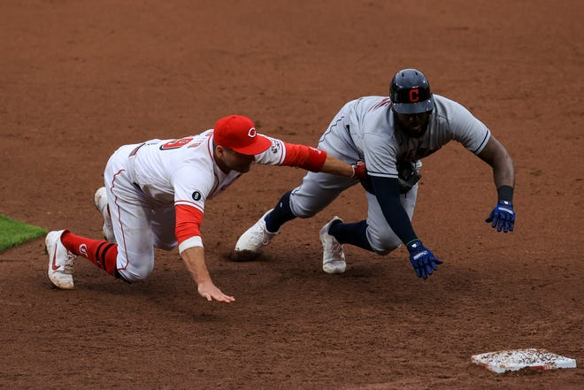 Cincinnati Reds first baseman Joey Votto, left, dives and tags out Cleveland's Franmil Reyes, right, for the second out of a triple play on a line out by Josh Naylor in the eighth inning of the Reds' 3-2, 10-inning win Saturday. [Aaron Doster/Associated Press]
