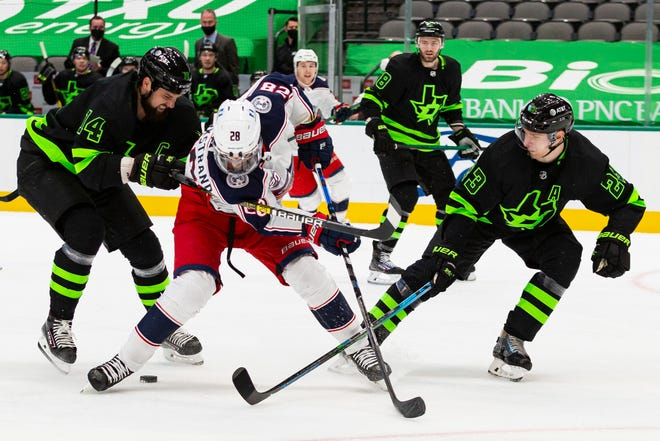Dallas captain Jamie Benn (14) and defenseman Esa Lindell (23) vie for control of the puck with the Blue Jackets' Oliver Bjorkstrand (28) on Saturday.